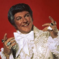 liberace wearing pianoring in white costume