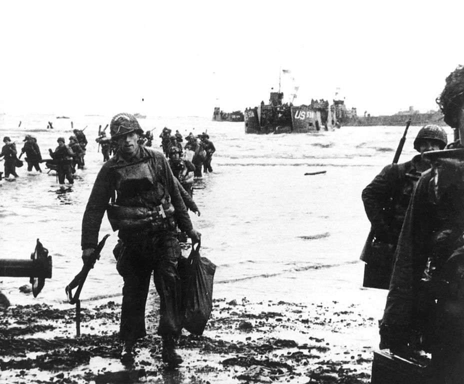 Carrying full equipment, American assault troops move onto Utah Beach. Landing craft can be seen in the background.